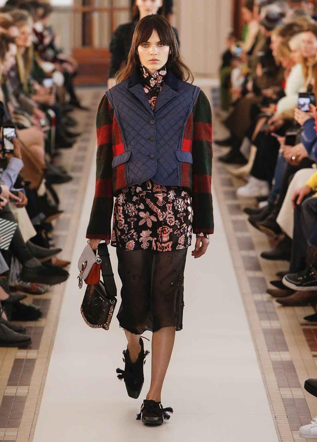 画像: 「クラシカルなハンティングジャケットをイメージした」というコンビネーションジャケットに、トランスペアレントなスカートを合わせて女性らしさを演出。ダブルで持ったバッグには、ラッキーチャームが COURTESY OF CARVEN