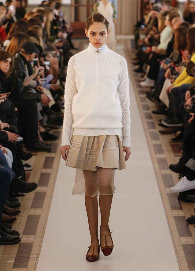 画像: 今シーズンを象徴するルックのひとつ。透かし編みのニットの下からハイネックのシャツがのぞく、どこか懐かしいトップスのスタイリングに対して、素材のコントラストを効かせたスカートが遊び心を感じさせる COURTESY OF CARVEN