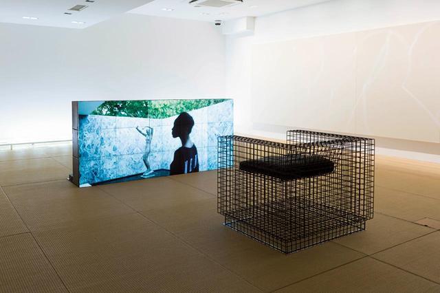 """画像: 建築家でもあるヴァージルのルーツをたどる映像作品。モダニズム建築の巨匠ミース・ファン・デル・ローエの「バルセロナ・パビリオン」でアフリカ出身の若者たちを自ら撮影した。手前の椅子もヴァージルのデザイン。 《""""non-cablechannel""""》(2018, Digital Media LED Panel & Chair 8 EDITIONS) PHOTOGRAPH BY KOICHIRO MATSUI"""