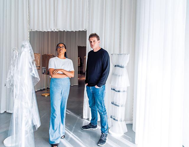 画像: 『反抗する身体』展覧会場にいるイギリス人アーティスト、アンセア・ハミルトンとデザイナーのジョナサン・アンダーソン。アンダーソンがキュレーターを務めたこの展覧会は、ウエストヨークシャーのヘップワース・ウェイクフィールド・ギャラリーで6月18日(日)まで開催中。シアー素材のウェアは、ロエベとJ.W.アンダーソンのアーカイブ。この展示室のテーマは「RevealingandProtecting.WipeClean(露出と保護。ワイプクリーン)」