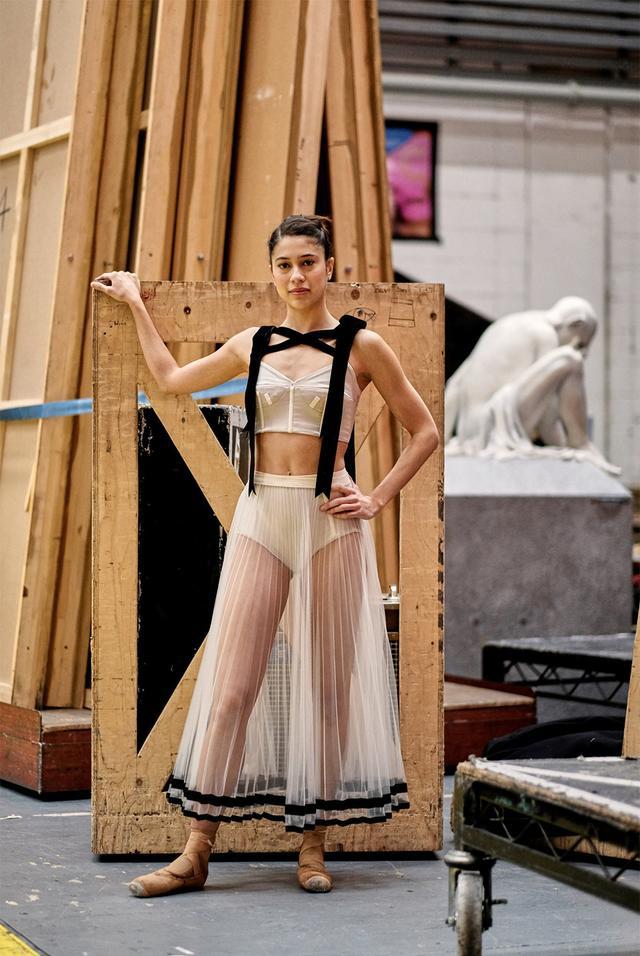 画像: 木曜日 14:10「衣装を身につけて」 「Corybantic Games(コリュバンテスの遊戯)」の衣装リハーサル初日を終えた、ファースト・ソリストのベアトリス・スティックス=ブルネル。英国ロイヤル・オペラ・ハウスのバックステージにて。胸に巻きついたハーネスのようなリボンは、舞台上でプリンシパル・ダンサーを示す目印となる。彼女の後ろにある座像は、以前上演したバレエ作品で使われたセットで、ここに保管されている。
