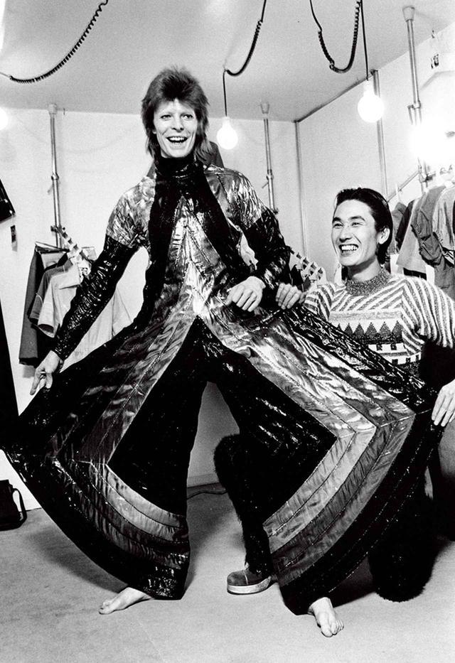 画像: 『ジギー・スターダスト』ツアーで来日したデヴィッド・ボウイと山本寛斎。寛斎のスタジオにて、1973年4月に撮影。ボウイが着ているのは、寛斎の制作した「スペース・サムライ」とでも呼びたいジャンプスーツ。日本の伝統的な紳士用着物である袴をベースにしてデザインしたものだ © MASAYOSHI SUKITA
