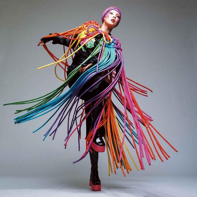 画像: 生地を折りたたんだり、プリーツをつけたり、ひねったりすることで、寛斎はたびたび三次元的な表現を追求した。写真でマリーが着ているドレスには、日本の伝統的な組み紐の技術を利用した編み込みとフリンジがあしらわれ、三次元的な効果と動きの両方が加えられている © HIROSHI YODA