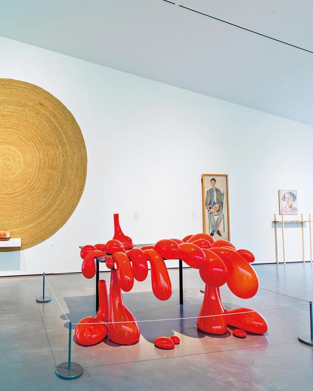 画像: ハミルトンの2014年の作品「VolcanoTable(火山のテーブル)」。吹きガラス製で、フェラーリ・レッド色の顔料、石灰岩タイル、粉体塗装したメタルを使用。『アンセア・ハミルトンが再考するケトルズ・ヤード』展用に彼女が制作した、草を手編みしたマットのシリーズも並ぶ