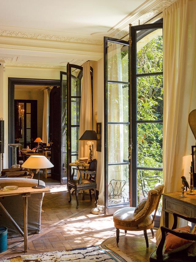 """画像: 背の高い窓の手前にあるのはナポレオン3世様式の""""乳母用椅子""""、 その向こうには緑の庭が広がる"""
