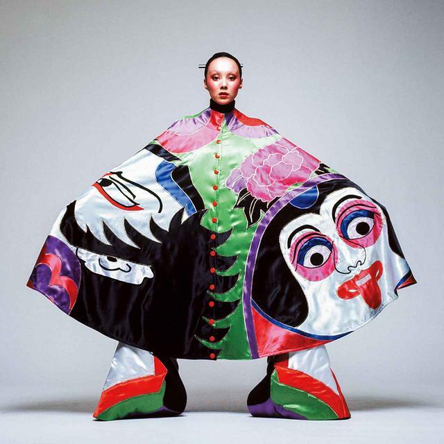 画像: 奴(やっこ)の隈取りが描かれた ケープを着たモデルのマリー。奴は、戯画化された姿で歌舞伎の舞台によく登場する。しかし、色使いは典型的な70年代のグラムロックテイストだ © HIROSHI YODA