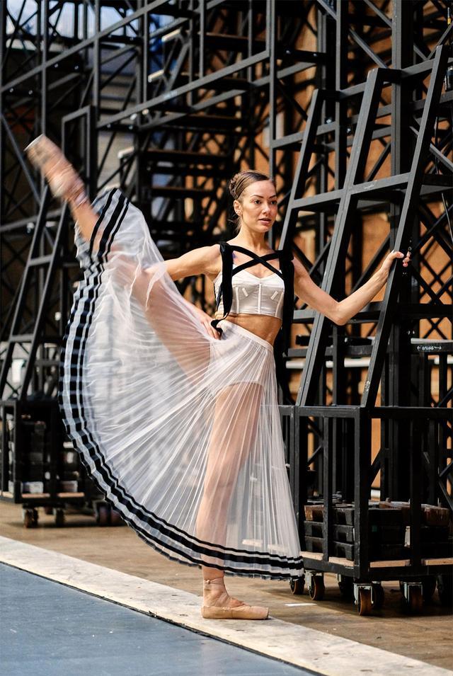 画像: 木曜日 9:55「足を真横に高く上げて」 午前10時ちょうどに予定されているリハーサル開始前に、ウォーミングアップをするロイヤル・バレエ団のソリスト、ティエニー・ヒープ。英国ロイヤル・オペラ・ハウスのバックステージにて。ダンサーたちがコスチュームを身につけるのはこれが初めて。