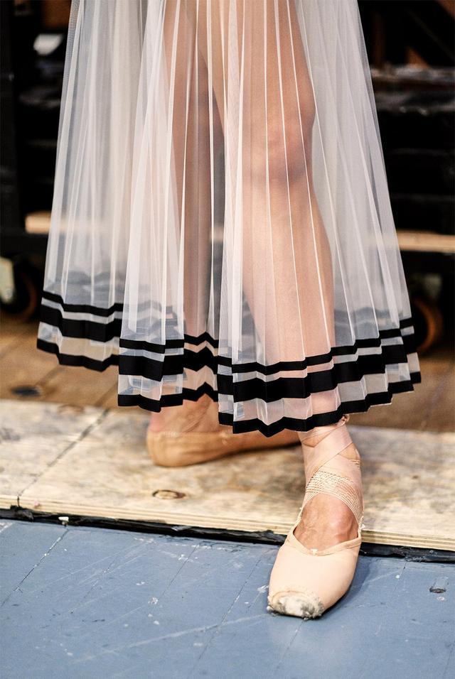 画像: 木曜日 13:20「第4ポジション」 バックステージで脚のウォーミングアップをするダンサー。プリーツ加工を施されたチュールは、裾にベルベットのリボンがあしらわれている。このチュチュは、アーデムの2018年春夏コレクションからインスパイアされたもの。とはいえ、今回の英国ロイヤル・バレエ団とのプロジェクト全体のミューズ的存在になったのは、音楽だった。アーデムは、レナード・バーンスタインの管弦楽曲を聴きながらコスチュームのスケッチをしたという。