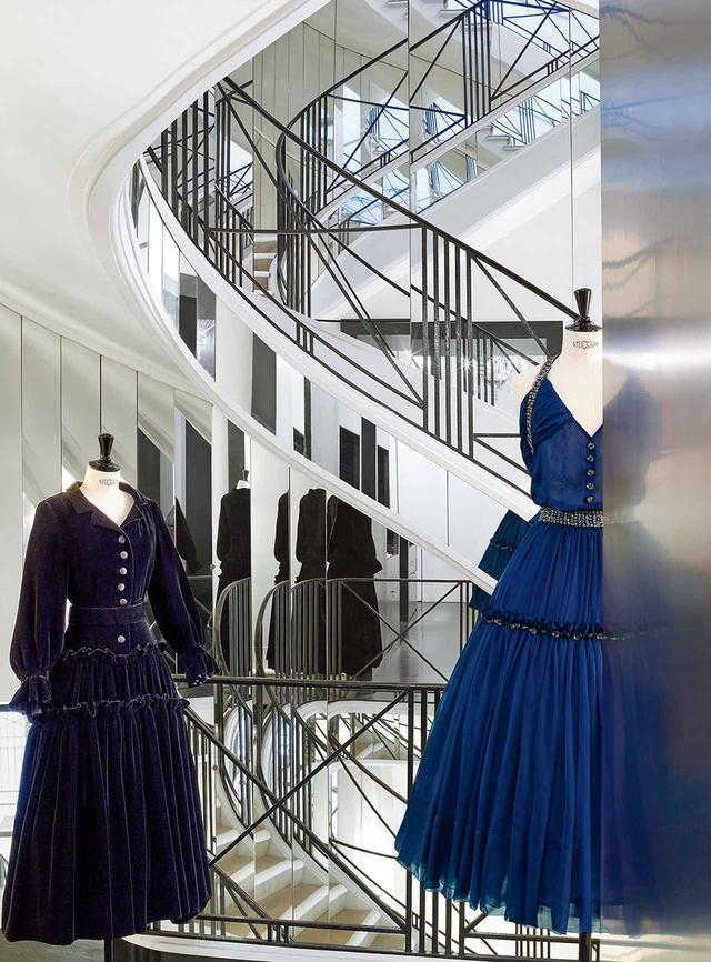 画像: パリ・カンボン通り31番地。文化省から歴史的記念物として指定されたシャネル本店の、オートクチュールサロンへと続く鏡張りの階段。1954-'55年秋冬オートクチュール・コレクションより、ガブリエル シャネルのキーアイテムであるリトルブラックドレス(左)。このドレスを着想源にした、カール・ラガーフェルドによる2017-'18年秋冬オートクチュールコレクションのドレス(右)。パリ郊外の北東部、パンタンにあるシャネルのアーカイブでは、5 万点以上の所蔵品が約15名のスタッフによって管理されている オートクチュールのドレス CHANEL HAUTE COUTURE / TEL.03(5159)5400