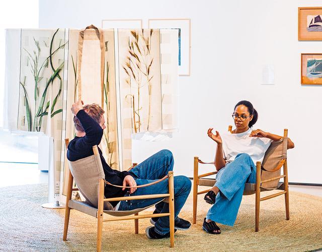 画像: アンセア・ハミルトンが再考するケトルズ・ヤード』展(現在は終了)の会場で、椅子に腰かけるアーティストとデザイナー。ハミルトンの2016年の作品「ブリティッシュ・グラッシーズ・キモノ」の前で