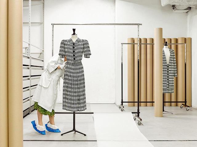 """画像: この撮影を行なったパリ市モード博物館のガリエラ宮では、ランバンのアーカイブをはじめ、6 万点以上の服と小物を保管。18℃に保たれた保管室はひんやりとしている。左は1939年にジャンヌ・ランバンがデザインしたドレス。右は元アーティスティック・ディレクター、ブシュラ・ジャラールによる、ランバンの2017年プレフォール・コレクションのアンサンブル。1939年のドレスと同じ""""ボワ・ジョリ""""柄を使用 (右)コート ¥345,000、スカート¥143,000 ランバン ジャパン(ランバン) TEL. 03(4500)6172"""