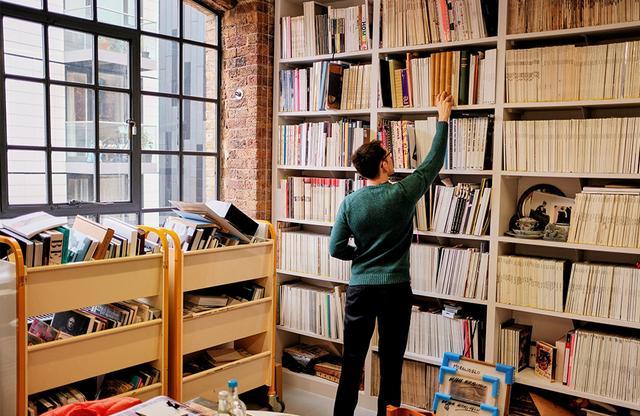 画像: 金曜日 9:30 「バックナンバー」 イースト・ロンドンにある自らのアトリエで、アーデムは保存用のコピーを取ろうとファッション誌『THE FACE』に手を伸ばした。アルファベット順に整理された書棚とブックカートには、アートブックや雑誌のバックナンバーがずらりと並ぶ。彼の右には母親の写真が飾られ、その手前には、エドワード8世と結婚したウォリス・シンプソンの磁器のティーセットが置かれている。