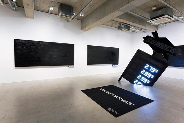 """画像: 初個展のテーマは広告。黒一色のオイル・ペインティングには実在する企業のロゴがつけられている。 左から時計回りに、《""""Lamar""""》《""""JCDecaux""""》(ともに2018, Oil on canvas 3200 ×1430mm)、 《""""dollar a gallon""""》(2018, Multi media 3418 × 1750 × 500mm)、 《""""oil spill""""》(2018, Carpet 1990×1720mm) PHOTOGRAPH BY KOICHIRO MATSUI"""