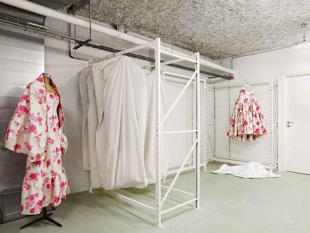 画像: バレンシアガのアーカイブでは、創設者クリストバル・バレンシアガの作品は白いキャラコの衣装バッグに入っている。一方、ニコラ・ジェスキエール、アレキサンダー・ワン、デムナ・ヴァザリアなど、21世紀の後継者たちの作品は黒い衣装バッグにしまわれている。これで両者の違いは一目瞭然だ。ヴァザリアによる2017-'18年秋冬コレクションのドレス(右)に使われたフラワープリント柄は、1964年のオートクチュール・コレクションに由来するもの。そのオリジナルである、フリルつきショールとシースドレス(左)もアーカイブの収蔵品である (右)ドレス(参考商品) バレンシアガ ジャパン(バレンシアガ) TEL. 0570-000-601 PRODUCTION: BIRD PRODUCTION. PHOTO ASSISTANT: WILLIAM MARSDEN