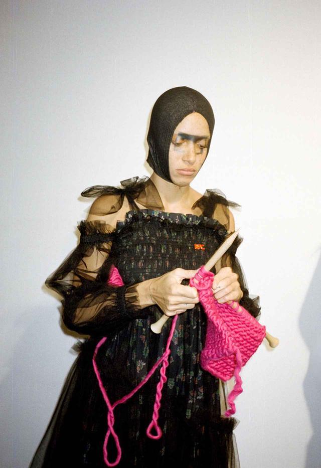 画像: 編み物はお手のもの|金曜日 PM4:55 編み物が好きなアジョワ。マティ ボヴァンのショーの空き時間を利用して、バックステージにあったウール アンド ザ ギャング(ロンドン発のニットブランド)の編み物キットをお試し中。