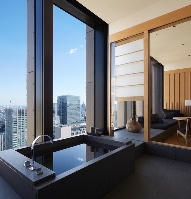 画像: スイートのバスルーム。木と紙と石を使ったアマンらしい内装で、バスタブは肩まで浸かれる日本流。奥にはリビングエリアが
