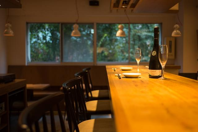 画像: 1枚板のカウンターからは街路樹が見える。お酒のラインナップは豊富で、「泡」も充実。写真はフランスのスパークリングワインで、1本¥4,500。ほかに長野県産シードル、ランブルスコと揃う。ドリンクメニューは、ウイスキーやワイン、紹興酒のほか、自家製シロップで作るレモンサワーや、ミントの代わりにパクチーを使うモヒートなども