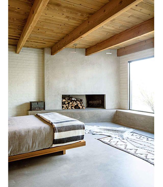 画像: 地元の家具職人ネイト・ダンフォースが、この家のすべての棚と、主寝室のチーク材のベッドを作った。暖炉の壁はしっくい、床に置かれた毛皮はトナカイ。ナバホ族の手織りの絨毯は1920年代のものだ。マットな風合いに磨かれたニッケル製の照明は、ポール・ルドルフのデザインによる、モジュライター社製