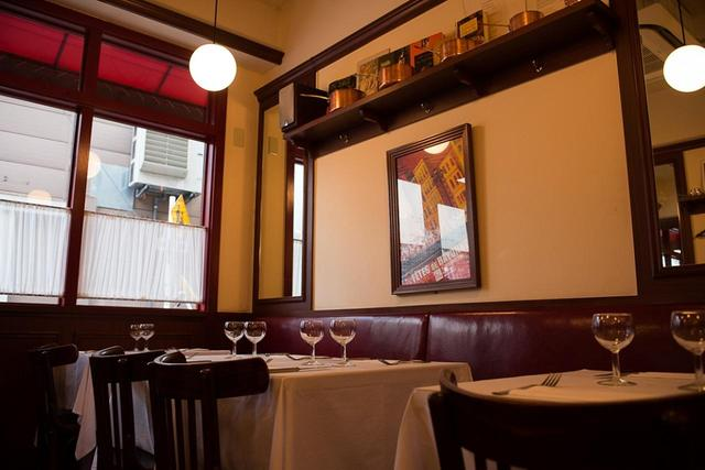 画像: 店内は、フランスのビストロそのもの。ボルドー色のベンチシート、白いカフェカーテン、背の低いワイングラス……。本場そのものの雰囲気を醸し出す。お客様に外国人ファミリーもよく見かける