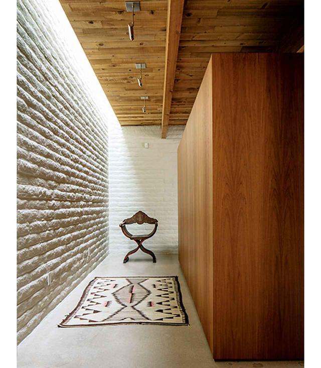 画像: 地平線 スコット・パスクのツーソンの自宅には、ぱっと目を引く劇場のセットのような仕掛けが施されている。たとえばこのヴィンテージのナバホ族の絨毯と、アンティークのサヴォナローラ・チェア(X型をした木製の折りたたみ椅子)が、白いモルタル加工のブロック壁とチーク材の壁に囲まれている光景が一例だ。床はコンクリートで固められている
