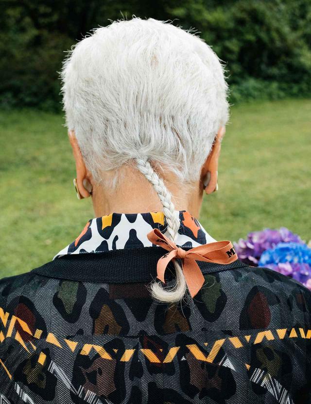 画像: アヒルの尾のように三つ編みにされ、ミッソーニのリボンで結ばれた髪は、彼女の個性的なトレードマークとなっている。でもそれは、ニットをジグザグや点描や縞模様を用いて万華鏡のような柄に変えてしまう彼女にとっては、とりわけ驚くべきことではない
