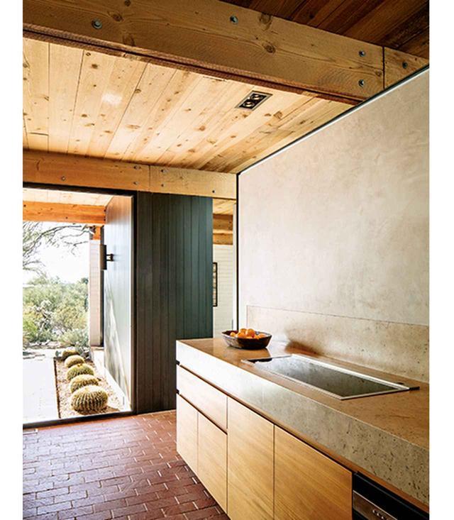 画像: キッチンの床は、もともと使われていたレンガに再仕上げを施した。カウンタートップにパスクが選んだのは、磨き抜かれたメキシコ産のトラバーチン。貯蔵庫の棚は、濃い色の羽目板のドアの後ろに隠されている。コンロはドイツのキッチン器具メーカー、ガゲナウのもので、キャビネットにはチーク材を使用