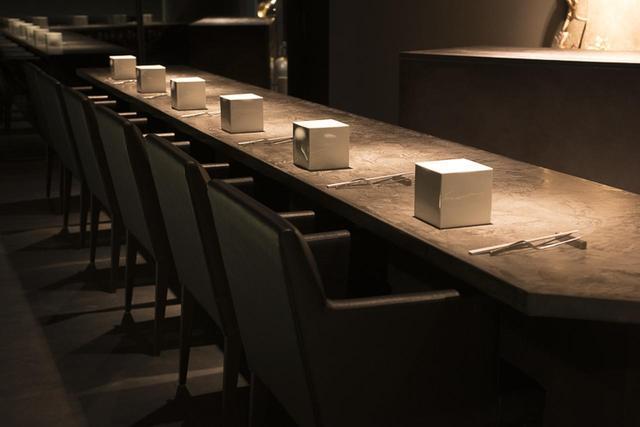 画像: カウンターに置かれているサービスプレートは、立方体の有田焼。ひとつずつ手作りで、「SECRETO」の文字が彫られている