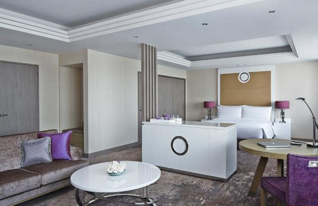 画像: ゆったりとした客室「エグゼクティブ プレミアデラックスキング」<76㎡>。白とパープルの高貴な色遣いに気品が漂う