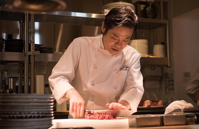 画像: 岡田賢一郎シェフ。1990年代、日本のレストランシーンを牽引したカリスマシェフが再び、キッチンというステージに戻ってきた。シェフズカウンターでは、シェフ自ら目の前で肉を切り、焼いてくれる