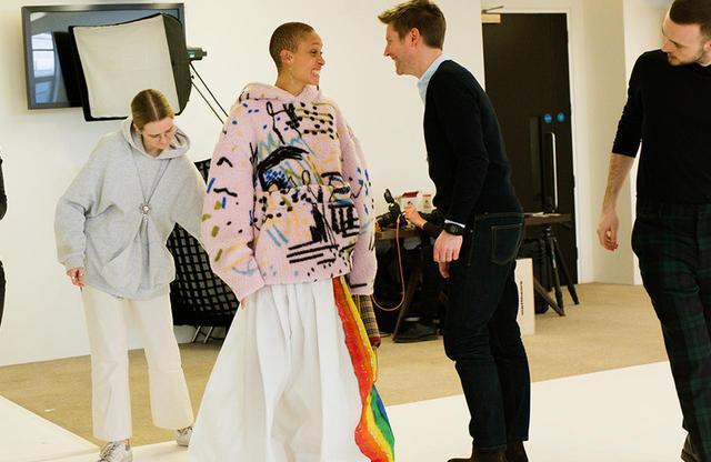 画像: 七色の虹|金曜日 PM2:10 バーバリーのプレジデント兼チーフ・クリエイティブ・オフィサーを退任することになったクリストファー・ベイリー。彼の最後のショーは、LGBTQ+コミュニティに捧げられたものだ。「ファッションは2018年のリアルを反映するものでないと」と、今回のコレクションについて語るアジョワ。「マーケティングの視点で作るべきだとは思わないけど、もし服を着ることで時代に合ったメッセージを伝えることができるなら、それは売れるに決まっているでしょう?」彼女がベイリーとおしゃべりしているあいだに、デザイン・アシスタントたちはシアリング素材のフーディトップスとワックスコットンのスカートの丈を、アジョワがつまずかないように調整していた。これがショーのオープニングルックになる予定なのだ。