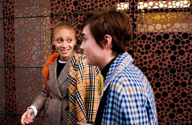 画像: チェック・メイト|土曜日 PM2:30 翌日の土曜日は、バーバリーのショーがある日。そしてアジョワは、新作のバーバリー・チェックのウェアを身にまとっていた。『VOGUE』の撮影のためウェスト・ロンドンにちょっと立ち寄ってから、アジョワは友人のカーラ・デルヴィーニュ(写真右)に会いに彼女の泊まるホテルを訪れた。カーラの部屋でシタビラメとマッシュポテトのランチを食べてから、二人は車に飛び乗りバーバリーのショーへと向かった。