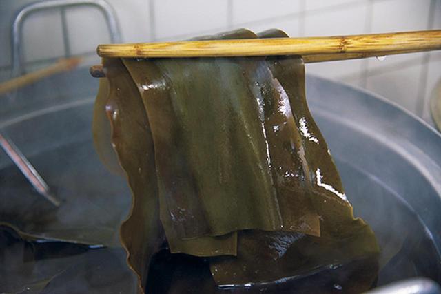 画像: 1. 大きな鍋にたっぷりと水を張り、昆布を入れ、2、3時間おいてから火にかける。約1時間65°Cくらいに保つ。海から引き揚げ、天日乾燥させた昆布は、ヨード臭が抑えられ、香気成分が飛躍的に高まるそうだ。長期熟成させた昆布を用いると、さらになだらかで含みのある、複雑かつおだやかな香りになる。「時間を経過したものには、香りに奥行きが出ます」と高橋さん