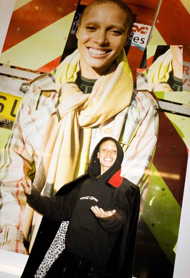 画像: 看板娘の凱旋|金曜日 PM2:05 バーバリーの洗練された本社ビルの受付エリアには、一面にユルゲン・テラー撮影の巨大なアジョワの写真が。この広告で彼女はアート・ディレクションも手がけた。この写真で唯一修正したのは、彼女が前歯につけているダイヤモンド製のシャネルのロゴマークを消したことだけだ。「このトゥースジュエリーは3年前につけたの」と笑うアジョワ。彼女は自分の写真の前でポーズをとってくれた。「これの前は、『PLAYBOY』のウサギマークをつけていたわ」。この瞬間をもっとよく見ようと、バーバリーの従業員たちがガラス製の階段に立ち止まり始めた。