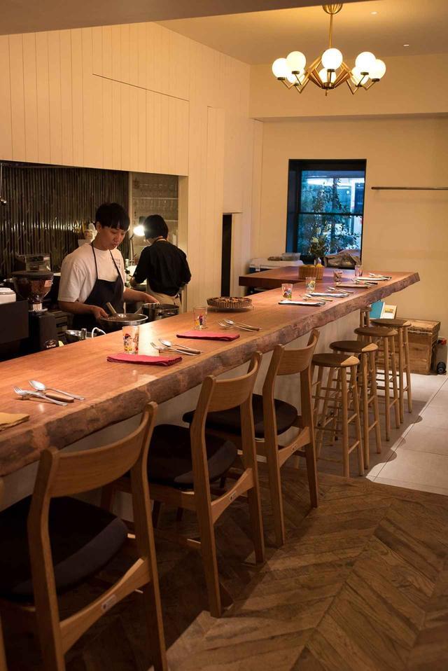 画像: 広々としたカウンターに座れば、侑子さんが料理している姿がよく見える。営業中は進太郎さんがサービス担当。手があけば料理もする。お店の雰囲気を決めているのが、目黒のインテリアショップ「COMPLEX」のオリジナルライト。温かみのある光に包み込まれるような安心感が