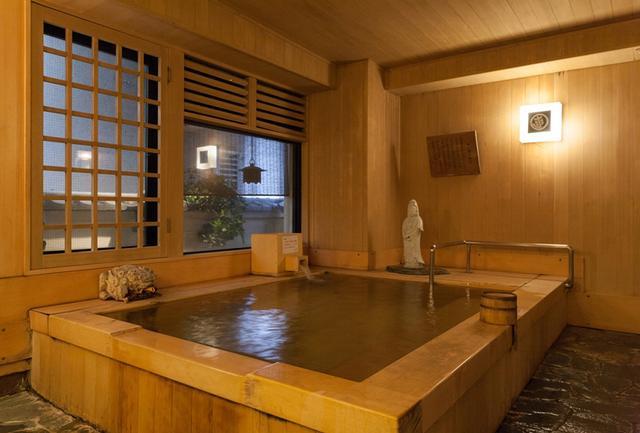 画像: ヒノキの香りに癒される共用の総檜風呂「桜が湯」。もう一つ、黒御影石の石風呂「ご福の井」もある PHOTOGRAPHS: COURTESY OF SADACHIYO SUKEROKUNOYADO