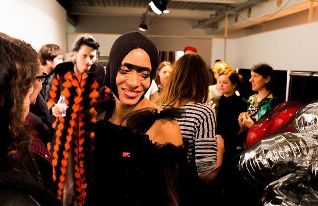 画像: ショーガール|金曜日 PM4:30 この日の夜、マティ ボヴァンのショーでアジョワはオープニングを務めた。写真は、そのチュールとツイードのルックに着替える前に撮ったもの(左後ろにはデザイナーのマティ・ボヴァンが写っている)。「いい意味で緊張するわ」と、ショーのオープニングを務めることについて語るアジョワ。「モデルの仕事で好きなことの一部はショーシーズンにあるの。この興奮とカオス、そして舞台へと歩き出す直前の静けさ。その一瞬は私のものになる――自分が先頭で歩くときは特にね」