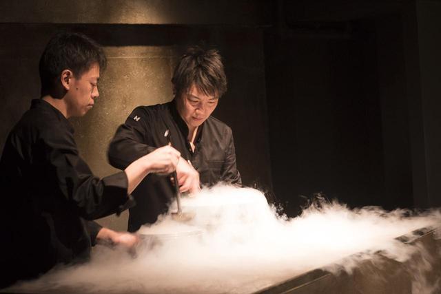 画像: ステージのようなキッチンで、液体窒素を使ってアイスクリームを作る薮中章禎シェフ(右)。石川県は能登の出身。能登直送の魚介類を使う