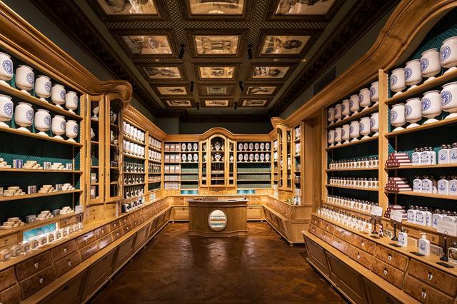 画像: 18世紀に調香師ビュリーがパリに創業した美容薬局を思わせる店内。オークや楡の重厚感漂う什器やヴェルサイユ式の寄せ木細工を用いた床などはすべて、フランス政府認定の伝統意匠を専門とする職人による手作り。棚に並ぶスキンケアのボトルやパッケージにもいにしえのパリのセンスが漂い、高い美意識を感じさせる空間だ