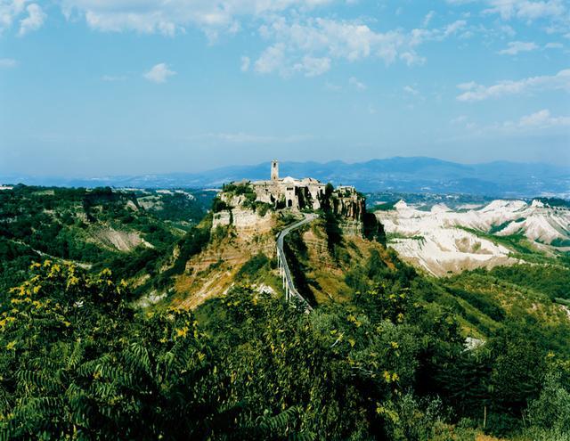 画像: 火山の噴火で積もった堆積物の頂高くに位置するいにしえの町、チヴィタ・ディ・バニョレージョの息をのむような絶景。今もこの町に住む数少ない住民たちが、過ぎ去った昔のイタリアの名残を継承している