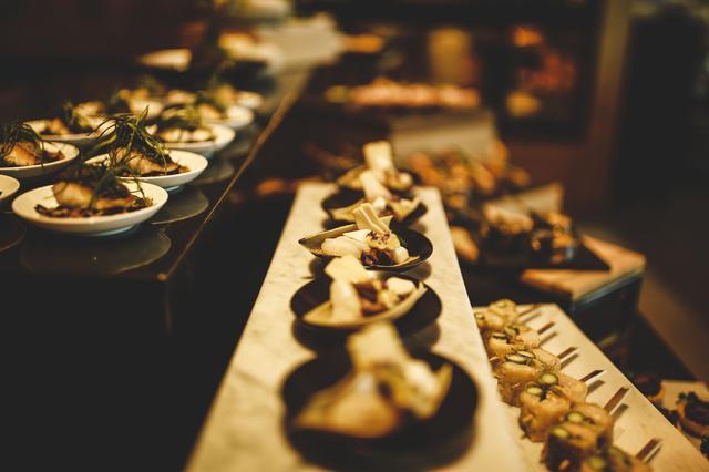 画像: アイランドキッチンでは、朝食、アフタヌーンティ、カクテルの各時間帯に軽食ブッフェを提供。カクテルタイムにはソムリエ厳選のワインセレクションとあわせて楽しむことができる