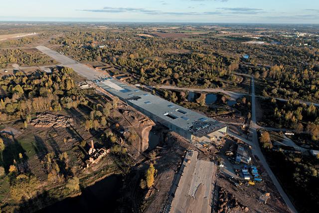 画像: 2006年に108の応募案の中からコンペに勝利。2013年3月から2016年2月まで36ヶ月をかけて、 かつてヨーロッパ最大とされた旧ソ連の空軍基地内、1.2kmの滑走路の延長線上にコンクリートと鉄骨による 建物が立ち上がっていった。左は空から見た2015年10月段階の現場写真。 その間、現場監修のため田根が毎月のように通ったタルトゥは人口10万人強、 エストニア最古の大学がある文化と学術の古都。20世紀初頭には今回ミュージアムが完成した一帯に、 ドイツ領事館を再利用した初代のミュージアムも存在した ©DGT.