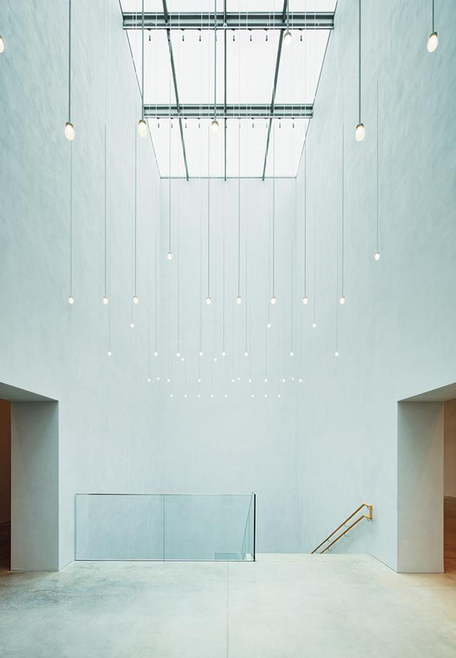 画像: 地下に向かう階段。トップライトの光を受け表情をあらわにする漆喰の壁、 白いピュアな空間に心が透き通る。手すりなど人の手が触れる部分にはオークが使われ、 温かな印象も醸す