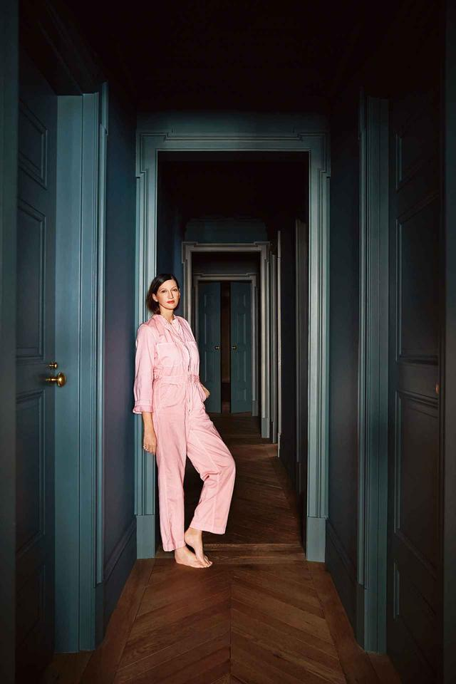 画像: 自宅の廊下に立つジェナ・ライオンズ。廊下の壁はイギリスの塗料メーカー、ファロー&ボール社製の「カード・ルーム・グリーン」という色で塗られている