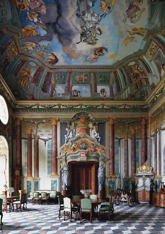 画像: ボールルームの壁のフレスコ画は、1750年にフィリップ・カール・ラウプマンが描いた。1885年には、プリンス・アルフレッド・フォン・リヒテンシュタインが、自身とその妻ヘンリエッテ、そして彼らの9人の子どもたちの絵を、壁画の登場人物として描き加えさせた。床にはルネサンス期に、3種類の違った石でできた菱形のタイルが敷き詰められた