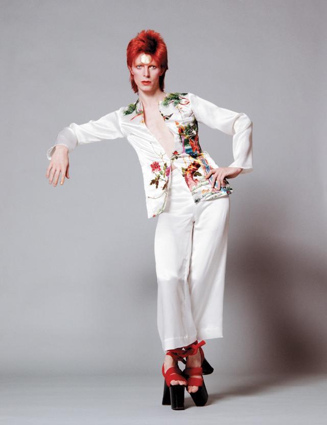 画像: 1973年に鋤田正義が撮影したボウイ。着用しているのは山本寛斎が『アラジン・セイン』ツアーのために用意した、刺しゅうを施したシルクのスーツだ。ボウイは1971年にロンドンでショーを行った山本のデザインに惚れ込み、同ツアーの衣装制作を依頼。このスーツも回顧展『DAVID BOWIE is』で見ることができる PHOTOGRAPH BY MASAYOSHI SUKITA