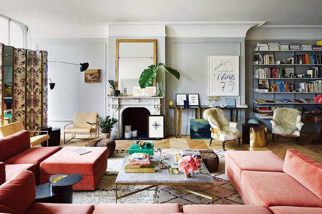 画像: ソーホーにあるジェナ・ライオンズのロフトアパートのリンビングルーム。ピエール・フレイのビロード生地で覆われた、ミロ・バーグマンのヴィンテージ・ソファ、大理石の天板が施されたポール・マッコブのコーヒー・テーブル、エルメスの生地が施されたディモーレ・スタジオの屏風、そして紙に描かれたサイ・トゥオンブリーの作品