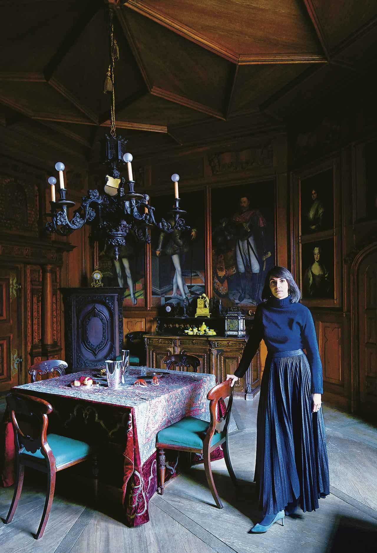 画像: 冬用のこぢんまりとしたダイニングルームに立つ、キュレーターのアリス・ストリ・リヒテンシュタイン。この部屋は、大きな部屋全体を暖房で暖めるのが難しかった頃に使用していた。銀のオブジェは、2017年に城に住み込んでいたデザイナーのひとり、ステファニー・ホーニックの作品。この部屋が初めて一般客に公開されたときの展覧会で発表された