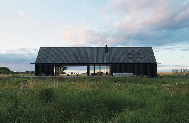 画像: イェンス・エンフロの建築事務所とDEVEアーキテクツが作った納屋のような家。ゴットランド島の典型的な牧草の生えた平地が、この家から流れて出ているかのように見える