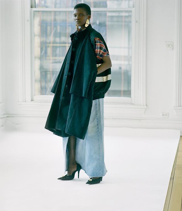 画像: バレンシアガのデムナ・ヴァザリアはベスト×カーコート (車の運転用のショートコート)、 デニムジャケット×トレンチというように、ふたつの服をジョイント。 服をたくさん着ればそれだけ安心感が得られるはずだという、 ヴァザリアらしいウィットとブラックユーモアが込められたデザインだ コート¥392,000、シャツ¥118,000 (参考価格)、デニムパンツ¥96,000、 パンプス(参考色)¥133,000、イヤリング(参考商品) バレンシアガ ジャパン(バレンシアガ) TEL. 0570(000)601