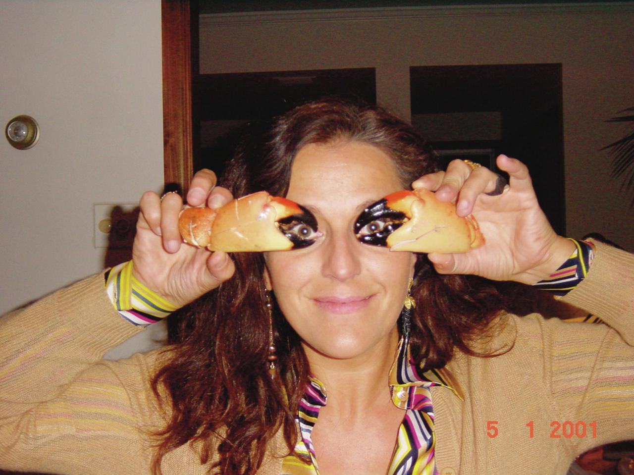 画像: 「フロリダで食べたカニの爪を手にした私。イヤリングが左右で違うのは、私の好みなの」 COURTESY OF MISSONI